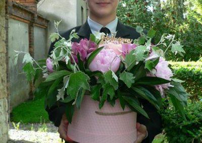 Uczeń stojący w ogrodzie szkolnym z koszem kwiatów.