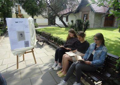 Uczniowie czytający książkę w parku